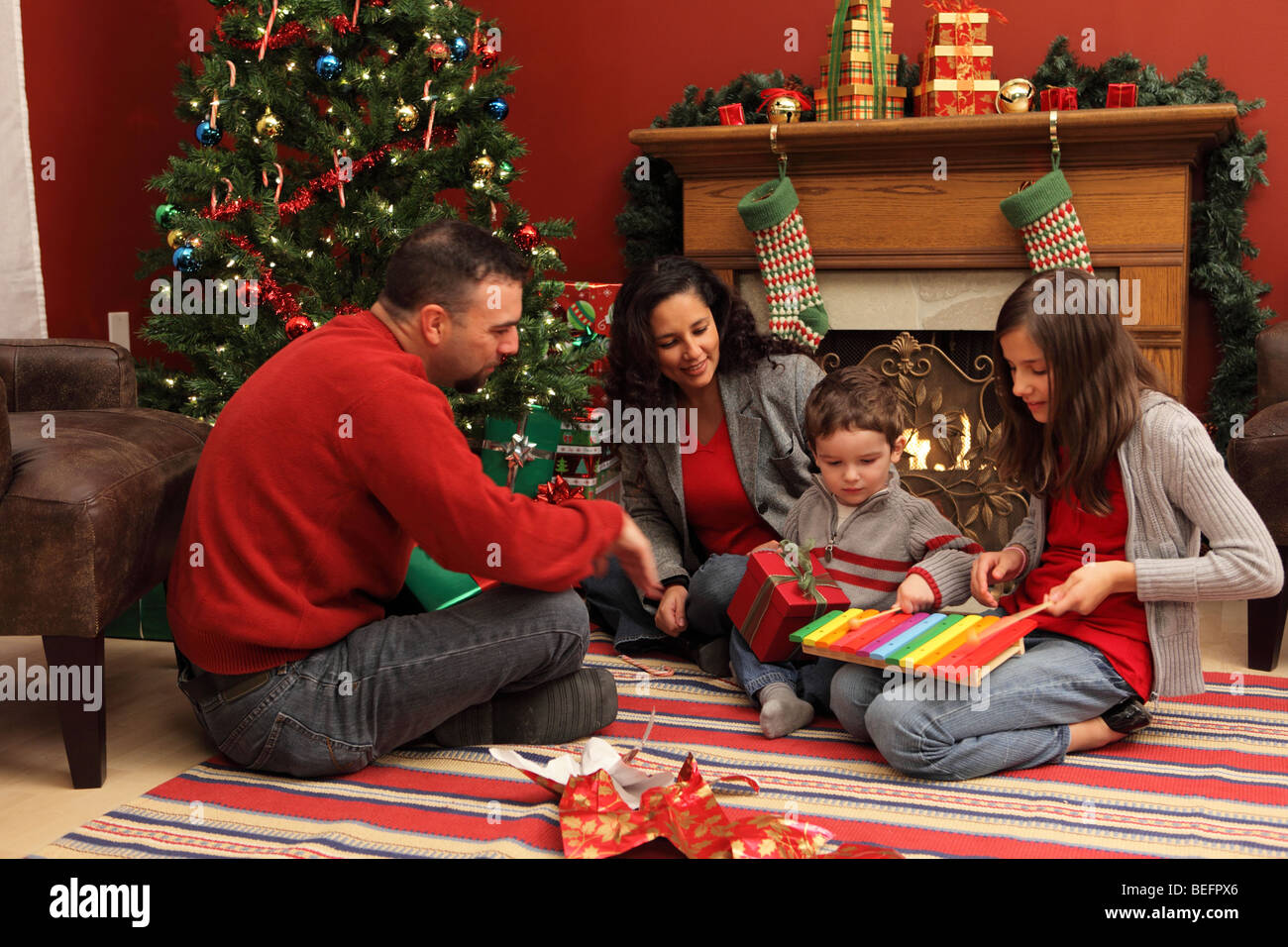 Family opening presents by Christmas tree - Stock Image