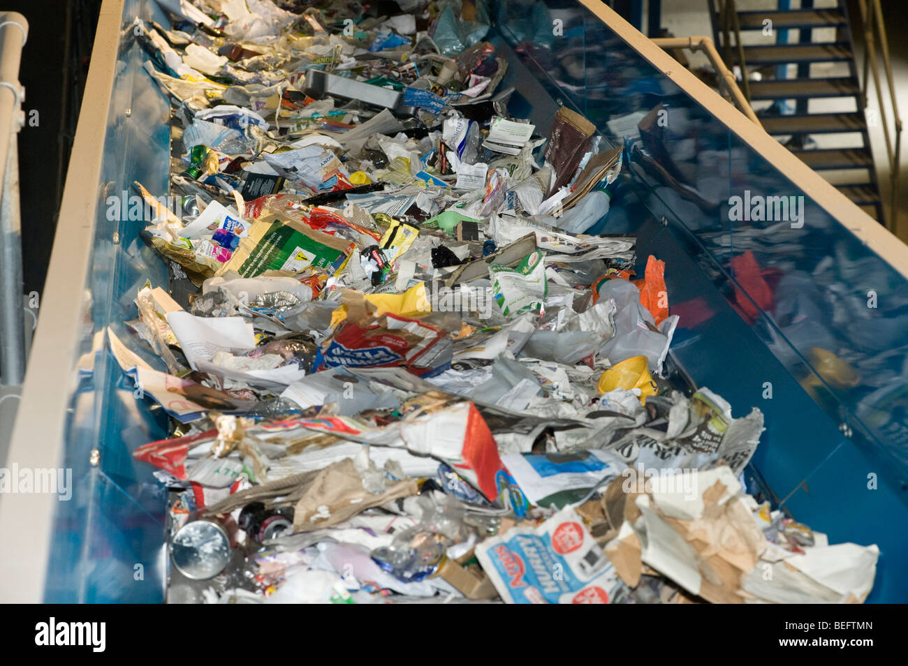 Rubbish on a conveyor belt for sorting at a recycling plant in the UK. - Stock Image
