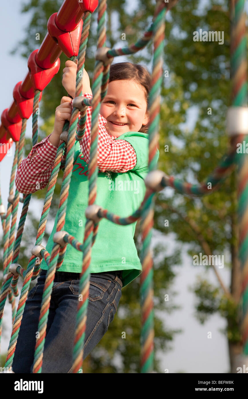 A girl is playing on jungle gym - Stock Image