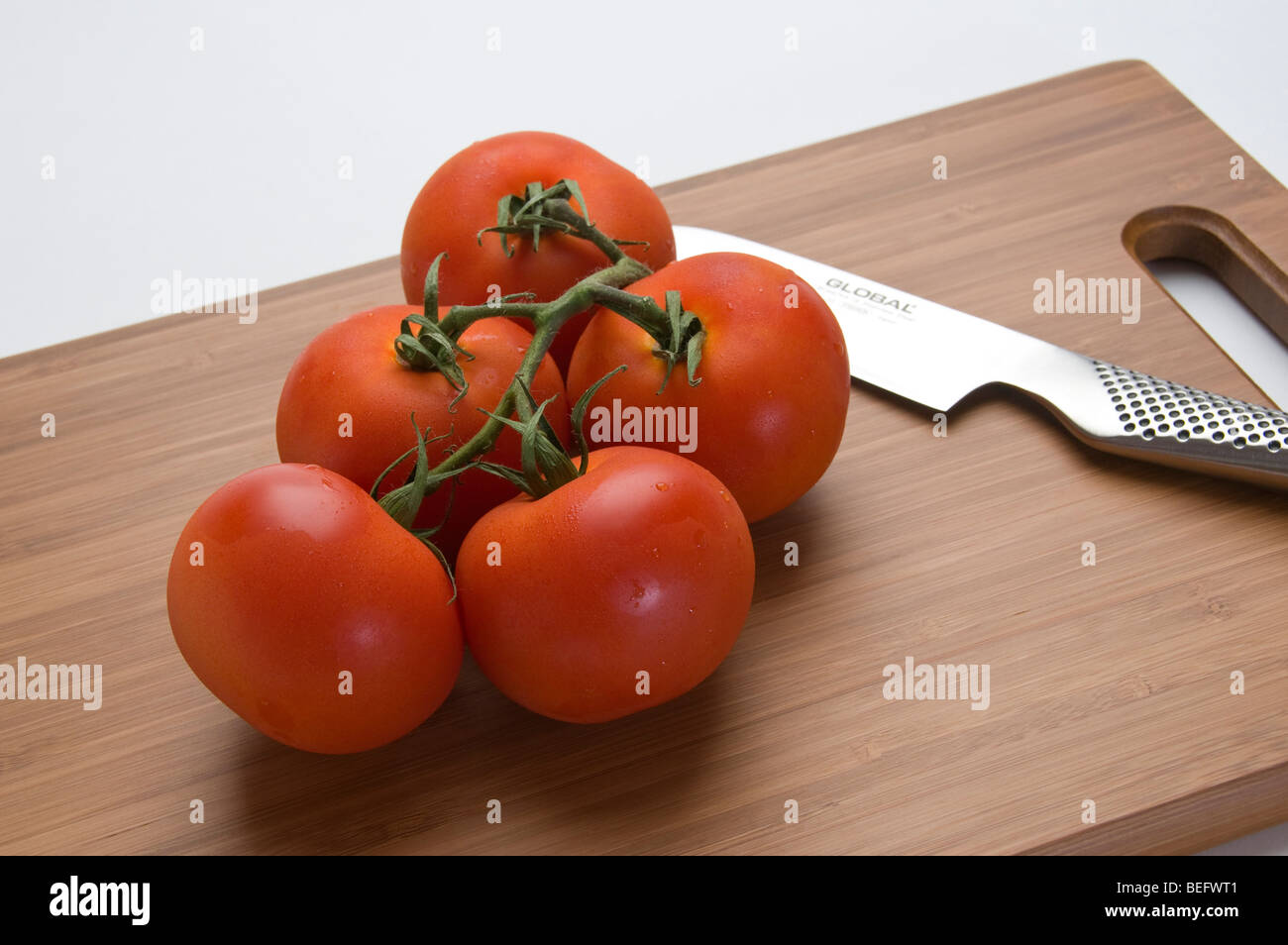 Organic vine tomatoes on cutting board. - Stock Image