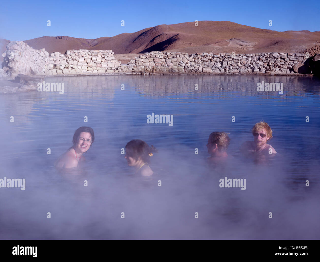 Tourists in the thermal springs at the Tatio Geysers in the Atacama Desert, Chile. - Stock Image