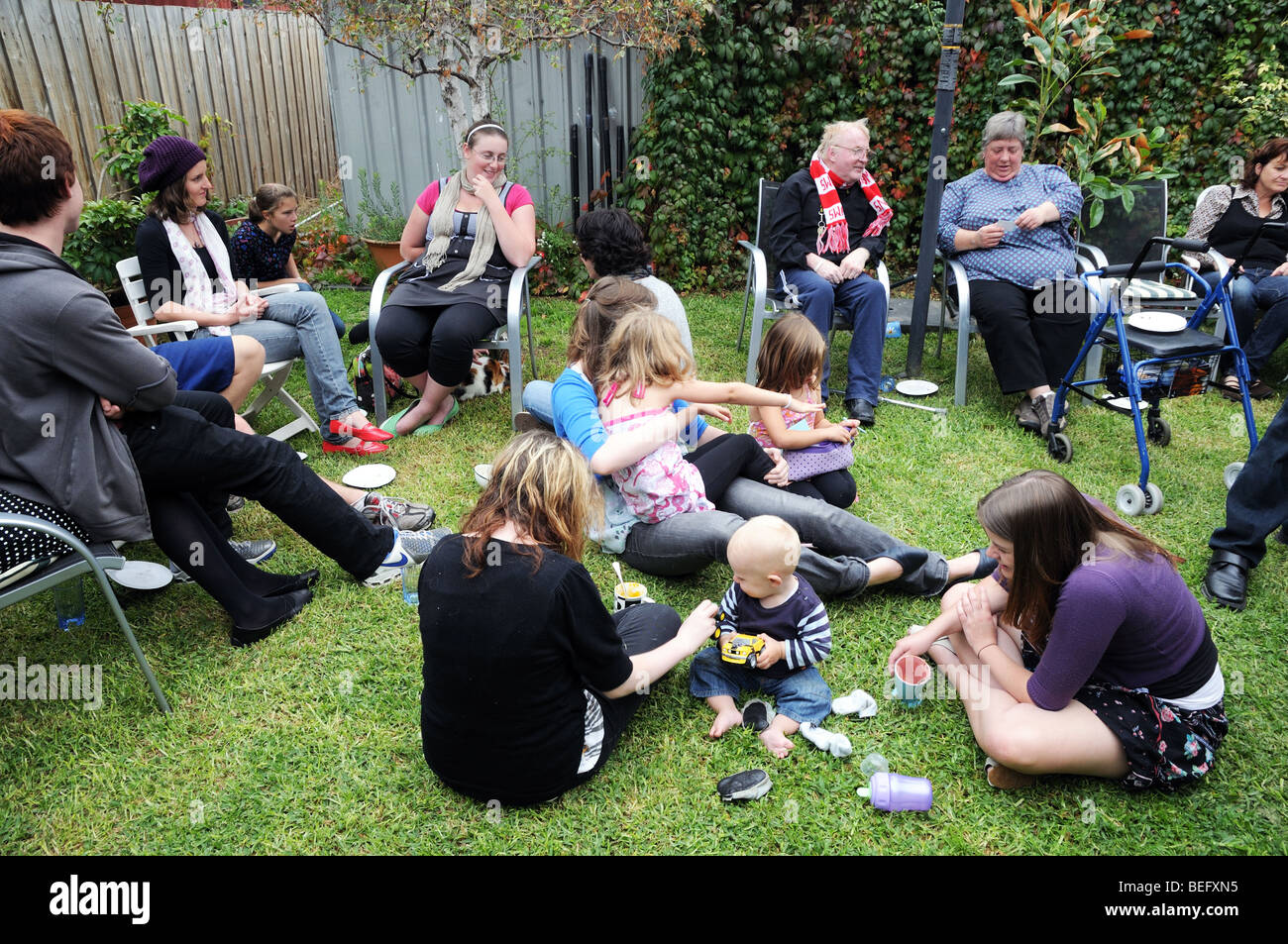 Australians enjoying Easter Sunday with a lunch time party of Hot Cross Buns and drinks in a private home and garden - Stock Image