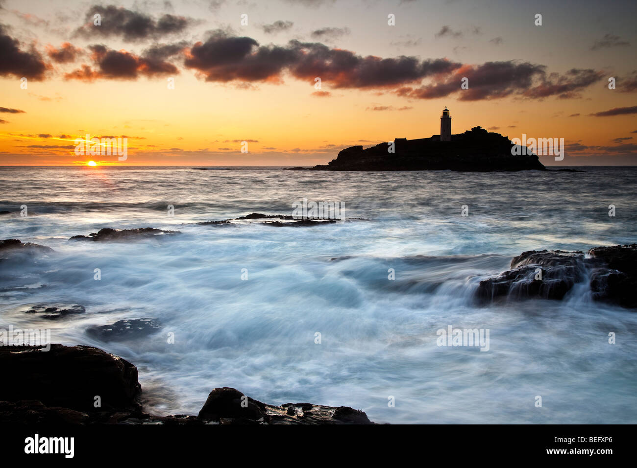 High Tide at Sunset, Godrevy Point and Lighthouse, St Ives Bay, North Cornwall - Stock Image