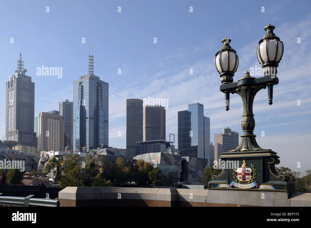 Cast iron lamp and coat of arms on Princes Bridge over Yarra River Melbourne Australia with high rise buildings - Stock Image