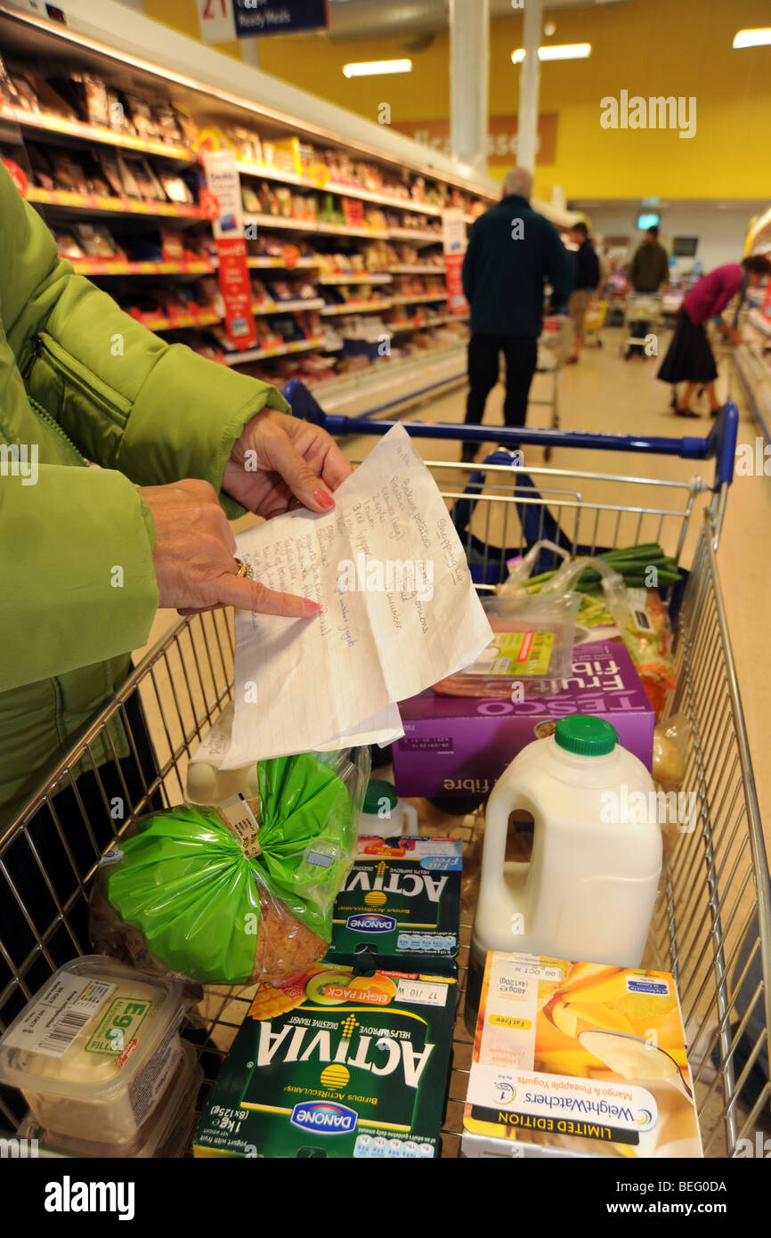 Shopping list with a  trolley in a supermarket - Stock Image