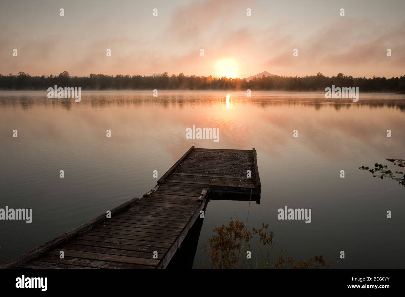 Sunrise at Lake Cassidy in fog with Mount Pilchuck and dock - Stock Image