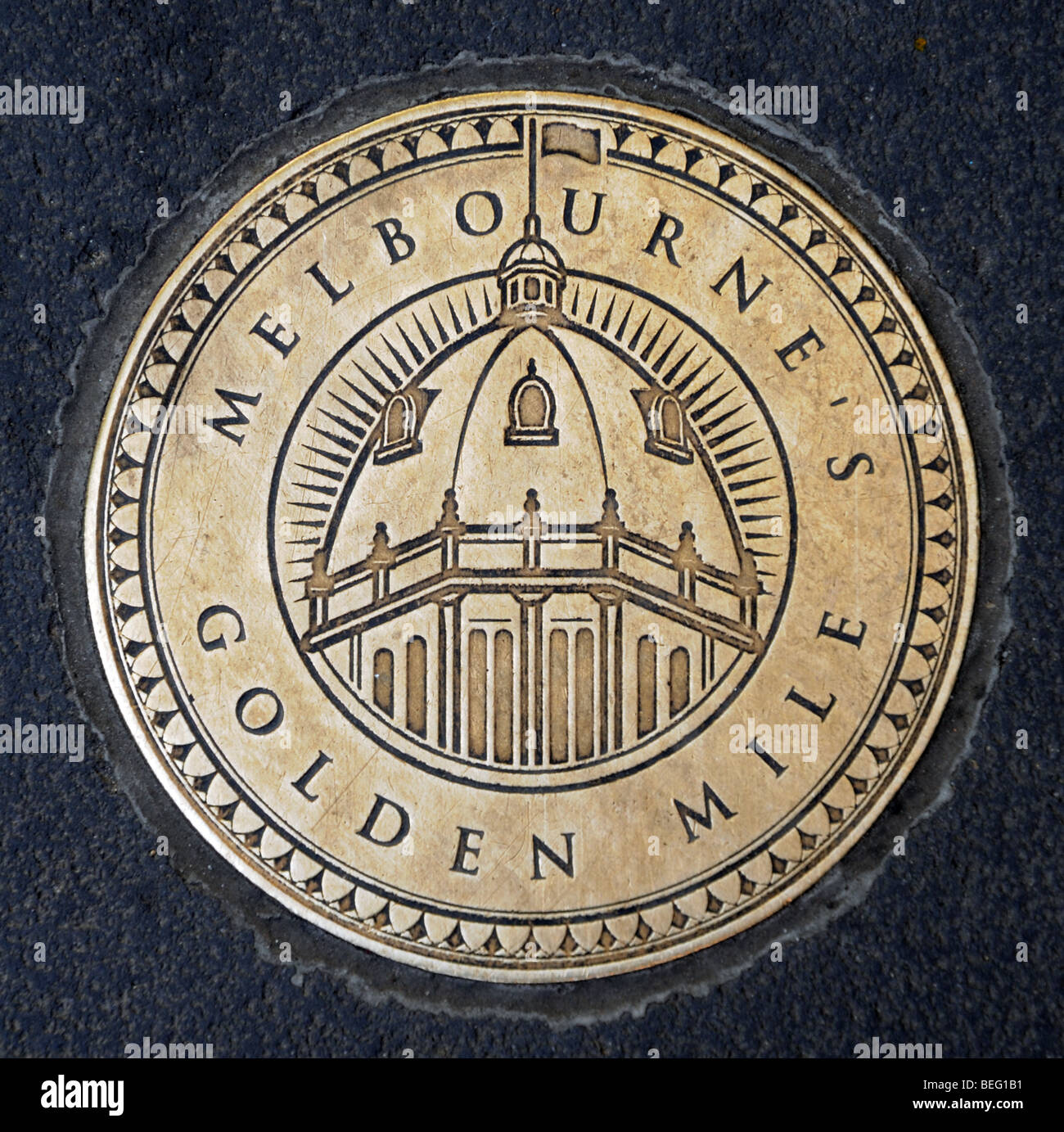 Brass medallion reading Melbourne's Golden Mile with engraving of dome on Flinders Station inset into pavement - Stock Image
