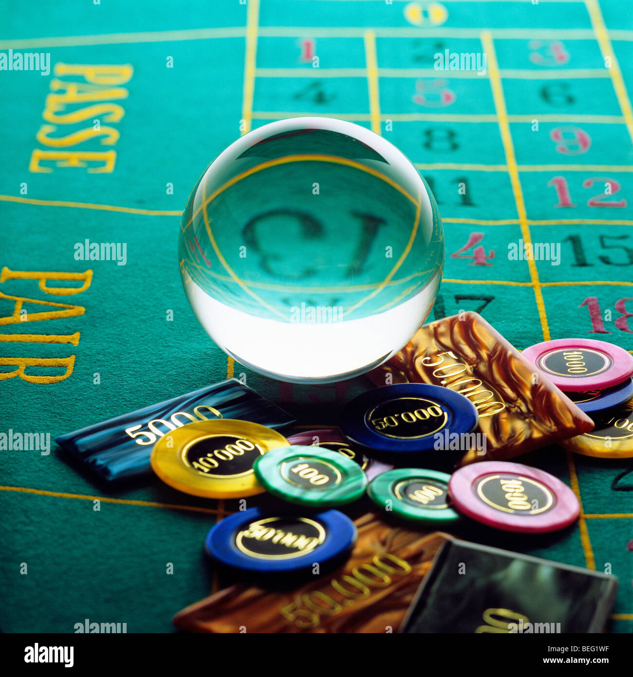 Crystal ball and gambling chips on roulette table - Stock Image