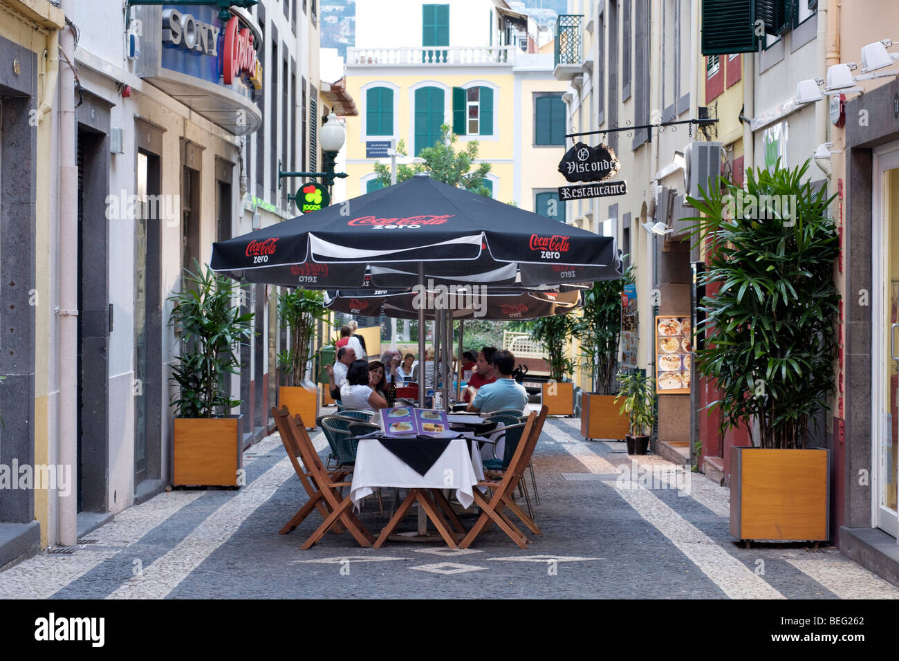 Restaurant tables on a pedestrian street in Funchal, Madeira. - Stock Image