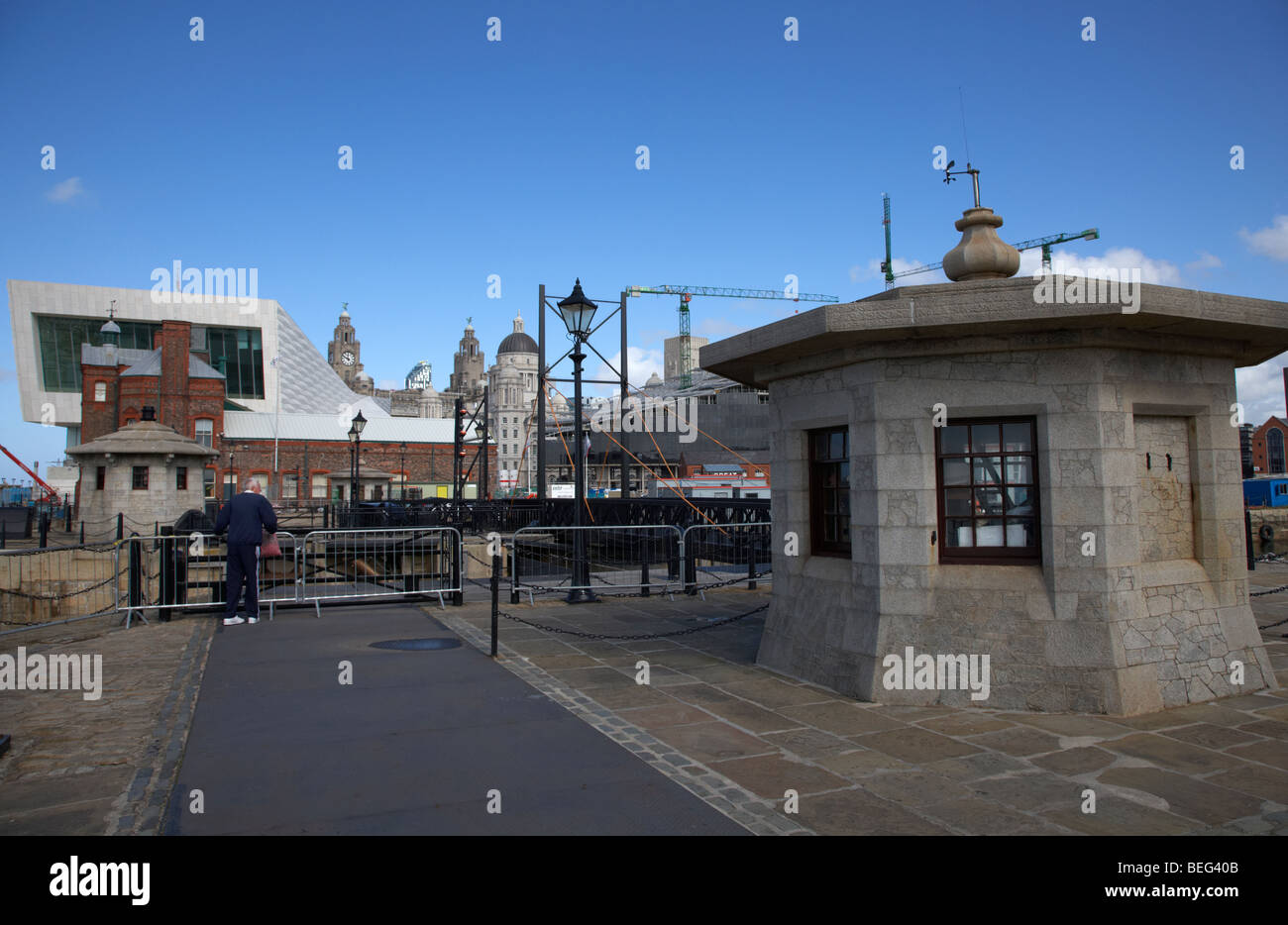tourist at the lock gates in the refurbished area at the albert dock liverpool merseyside england uk - Stock Image