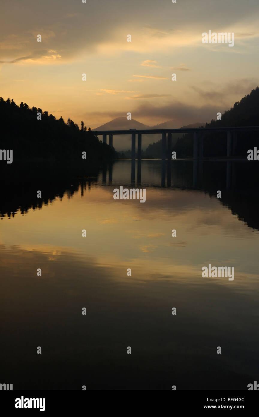 View of Jezero Bajer lake in Fužine (Gorski kotar, Croatia, Europe) and higway bridge in sunset with mountains in Stock Photo