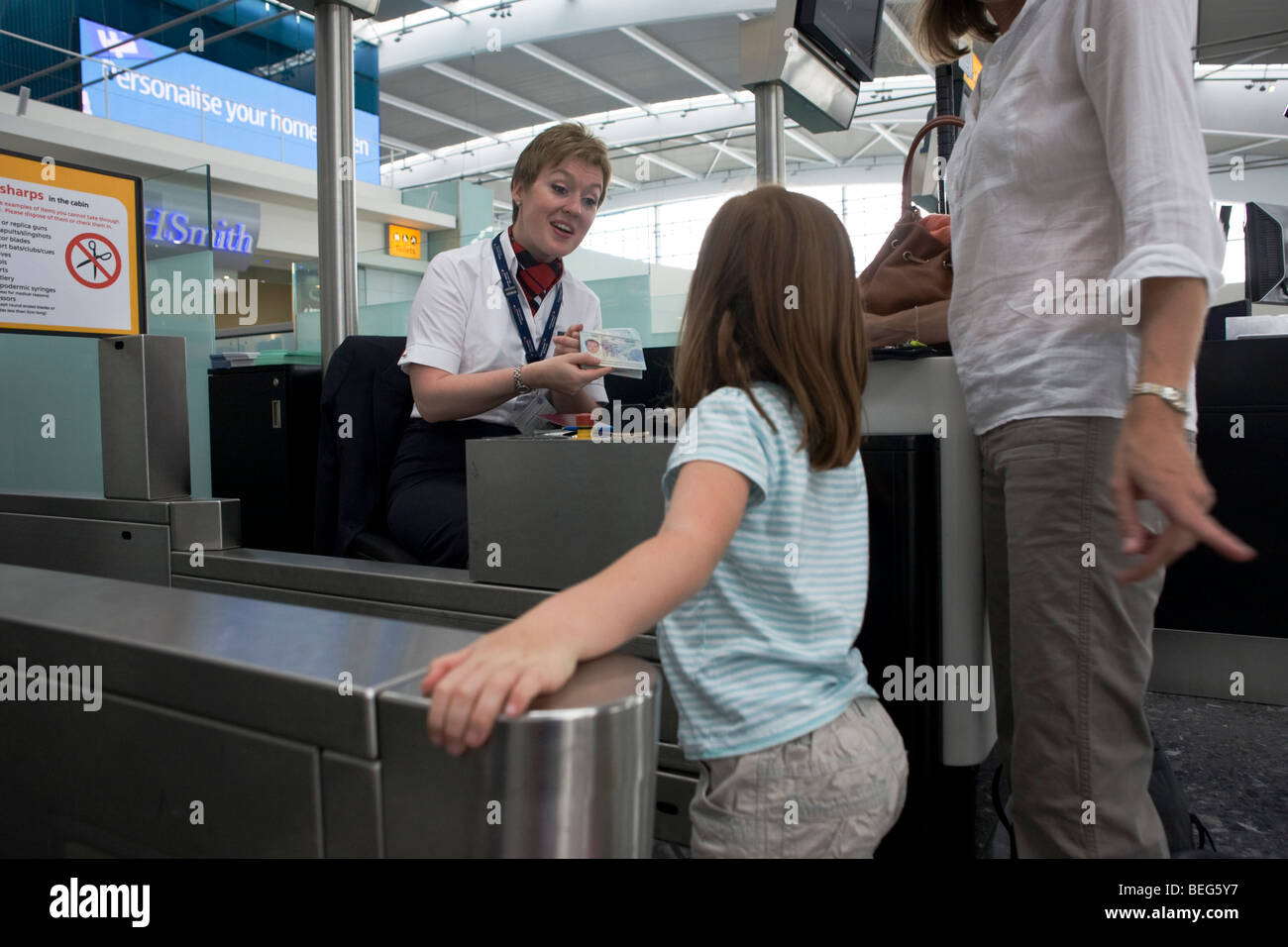 Young girl chatting with child-friendly British Airways check-in lady at Heathrow Airport's Terminal 5. - Stock Image