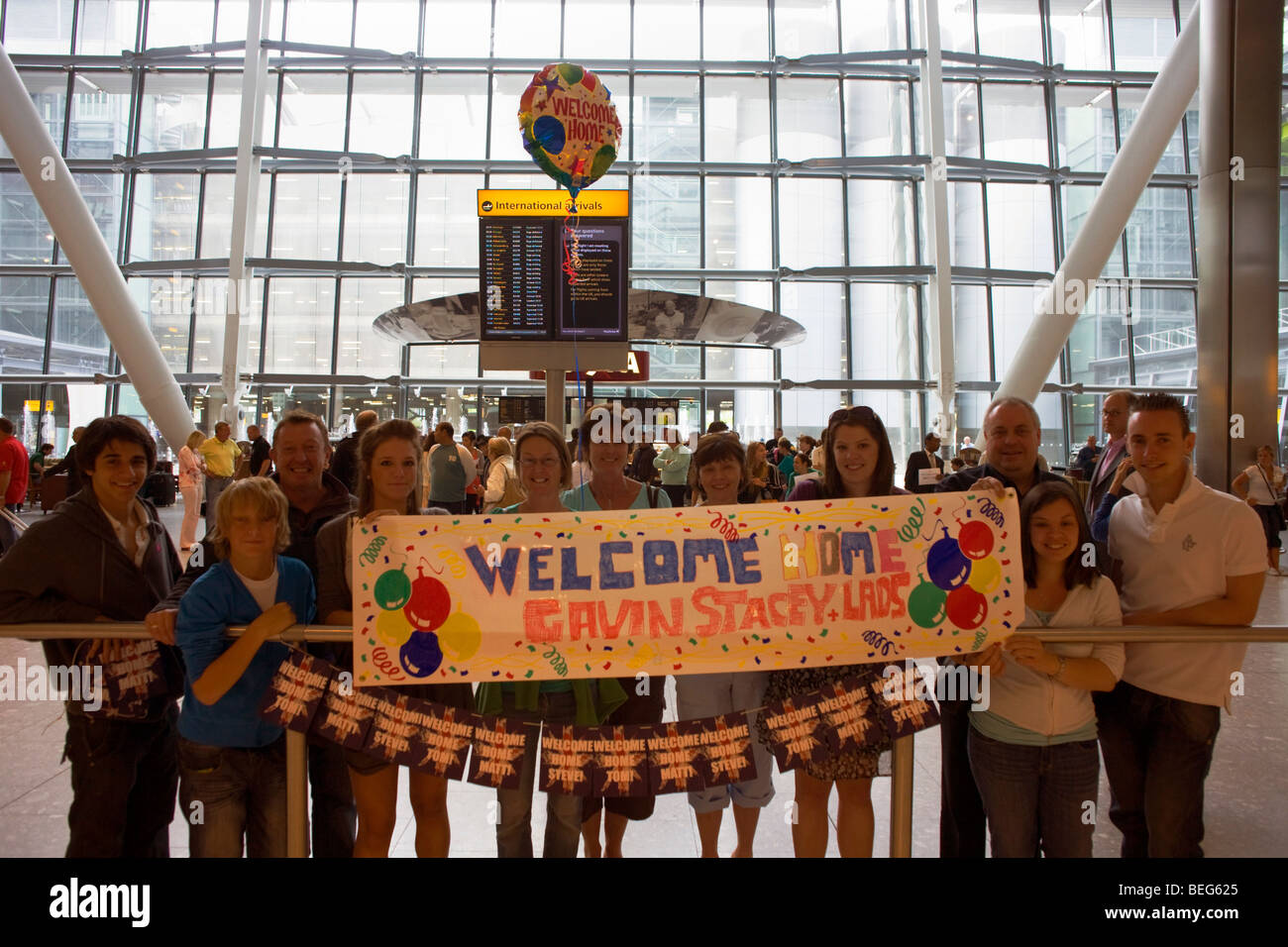 A family awaiting loved-ones in Arrivals of Heathrow's terminal 5 stretch a banner and float a helium-filled - Stock Image
