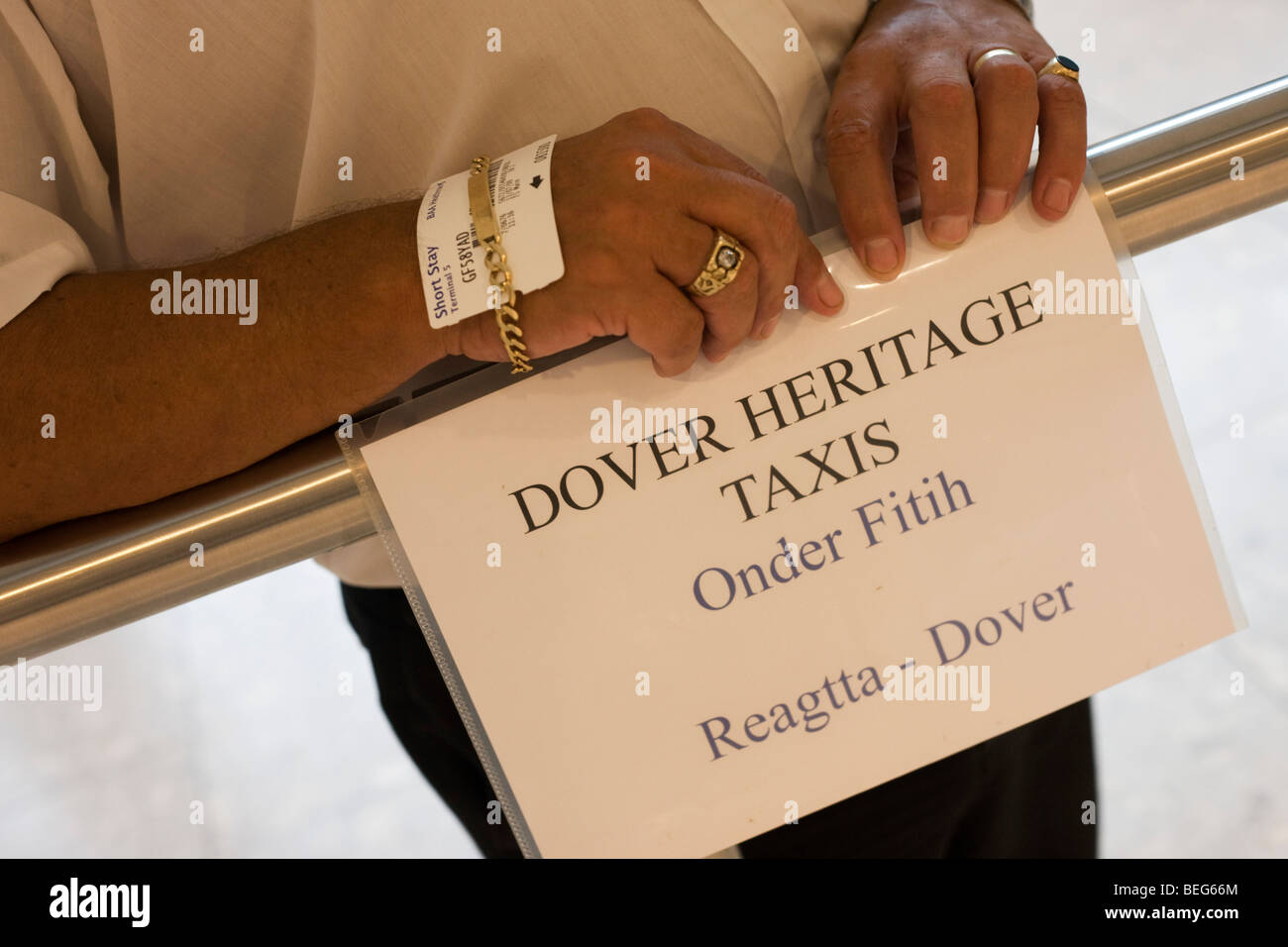 A greeting driver from Dover Heritage Taxis awaits his fare to arrive off a flight from Turkey in Heathrow Airport's - Stock Image