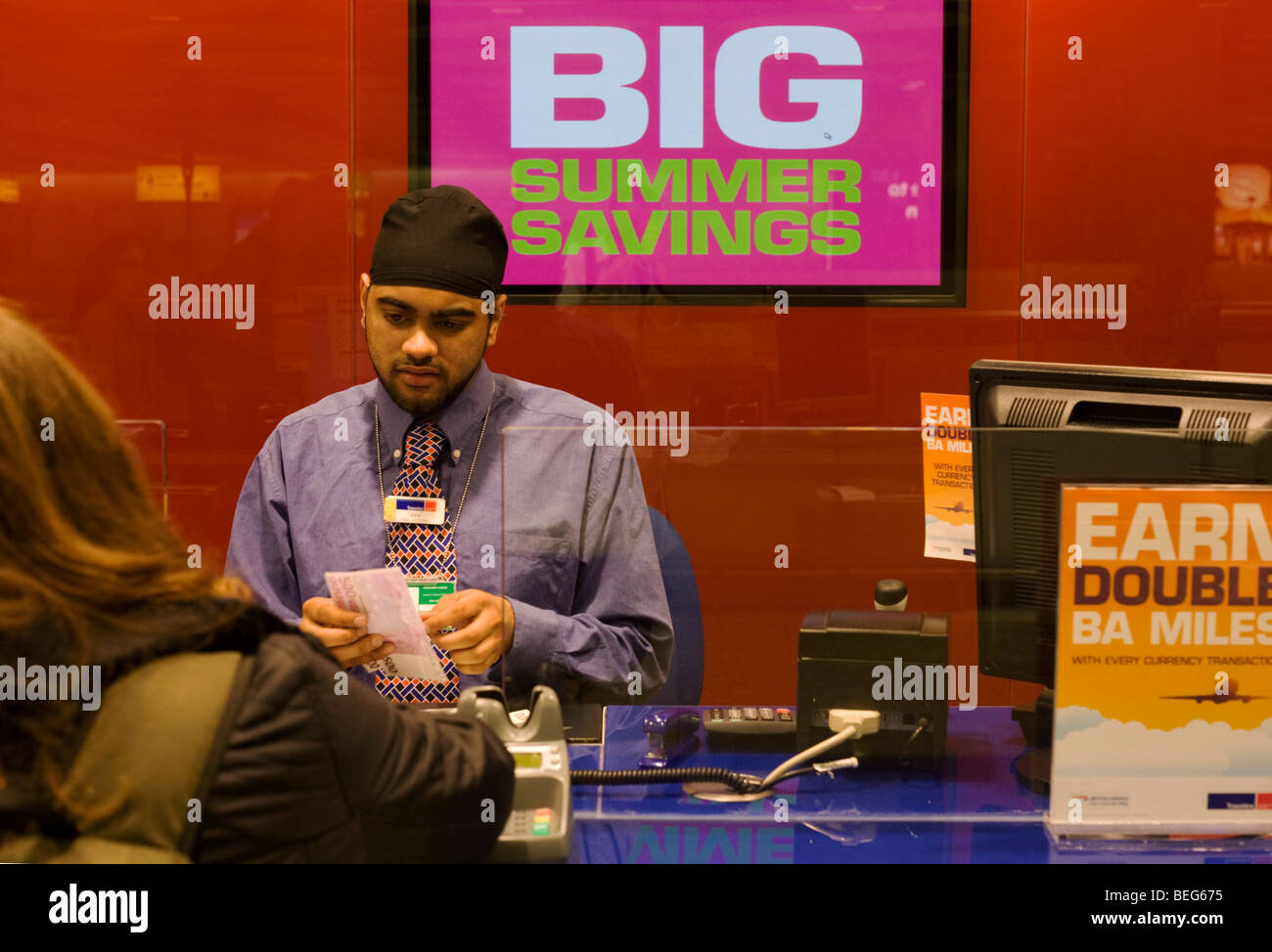 Travelex bureau de change assistant serves currency to passenger at Heathrow airport's terminal 5 - Stock Image