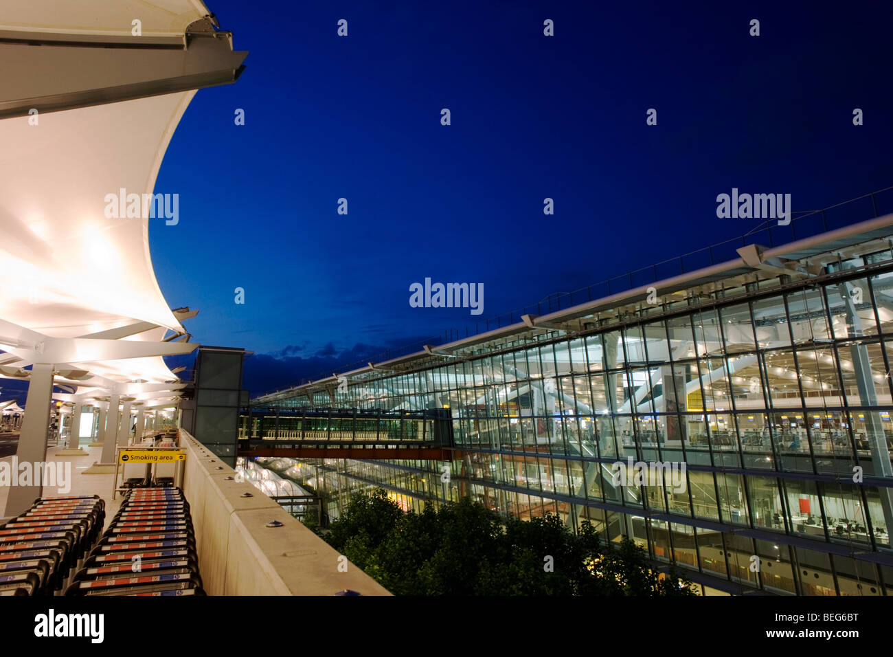 Early evening exterior of glass walls and glowing architecture of Heathrow Airport's Terminal 5, seen from departures - Stock Image
