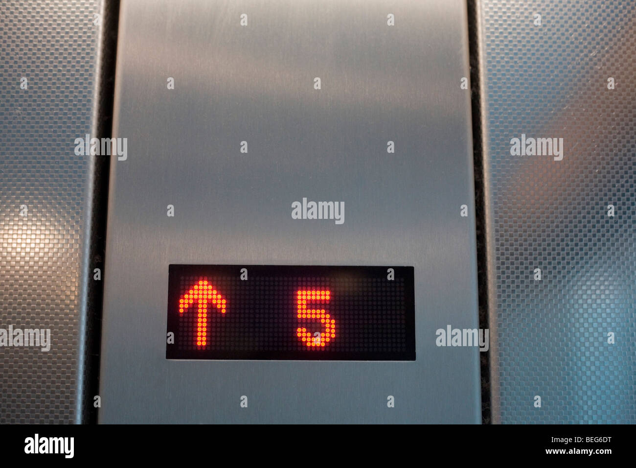 A lift (elevator) shows it is ascending to the top floor number 5 at Heathrow airport's Terminal 5. - Stock Image