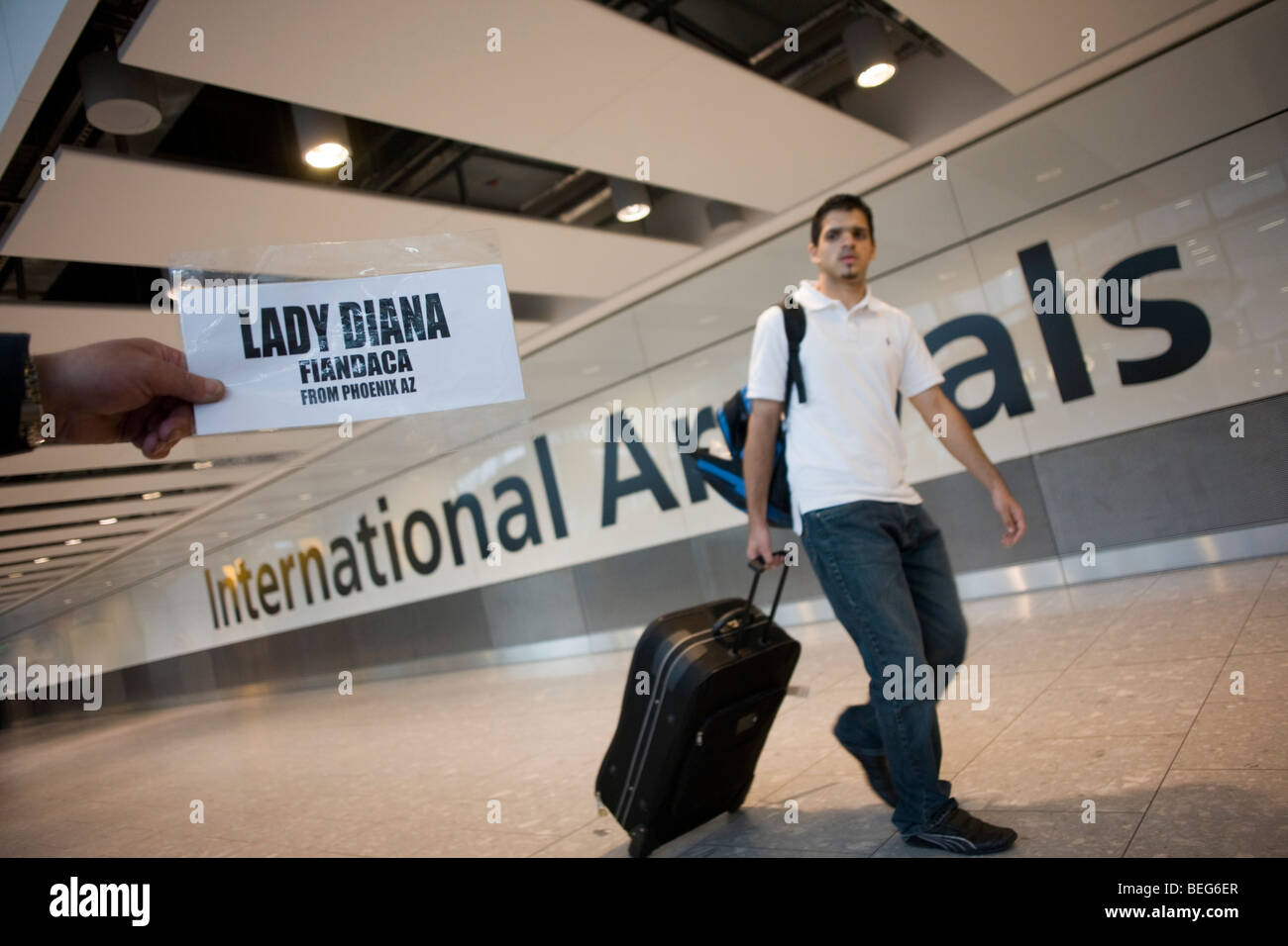 An unseen person holds out name card and awaits the arrival of a passenger on the ground floor of at Heathrow airport's - Stock Image