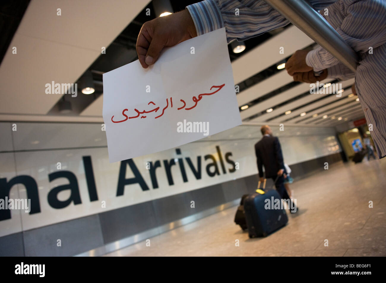 An unseen person holds out name card and awaits the arrival of a fellow-Kuwaiti on the ground floor of at Heathrow - Stock Image