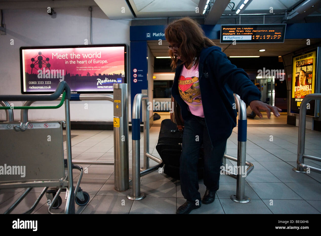 Heathrow Express passenger struggles through barrier in Heathrow train station at Heathrow's terminal 3. - Stock Image