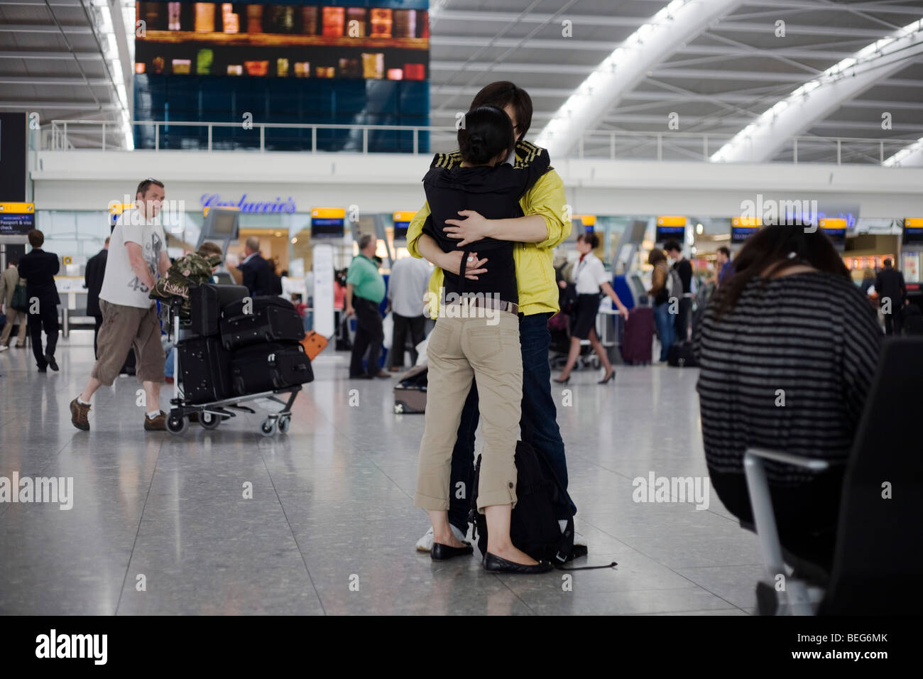 Young lovers say tearful farewells in departures concourse of Heathrow airport's terminal 5. - Stock Image