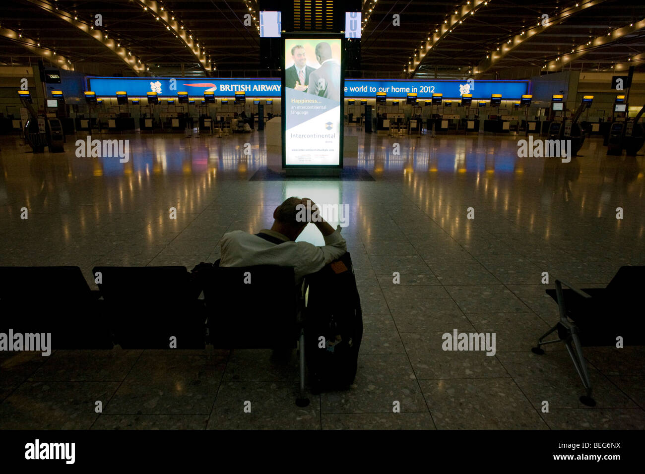 Stranded passenger awaits next flight in the morning from near-empty departures concourse at Heathrow's terminal - Stock Image