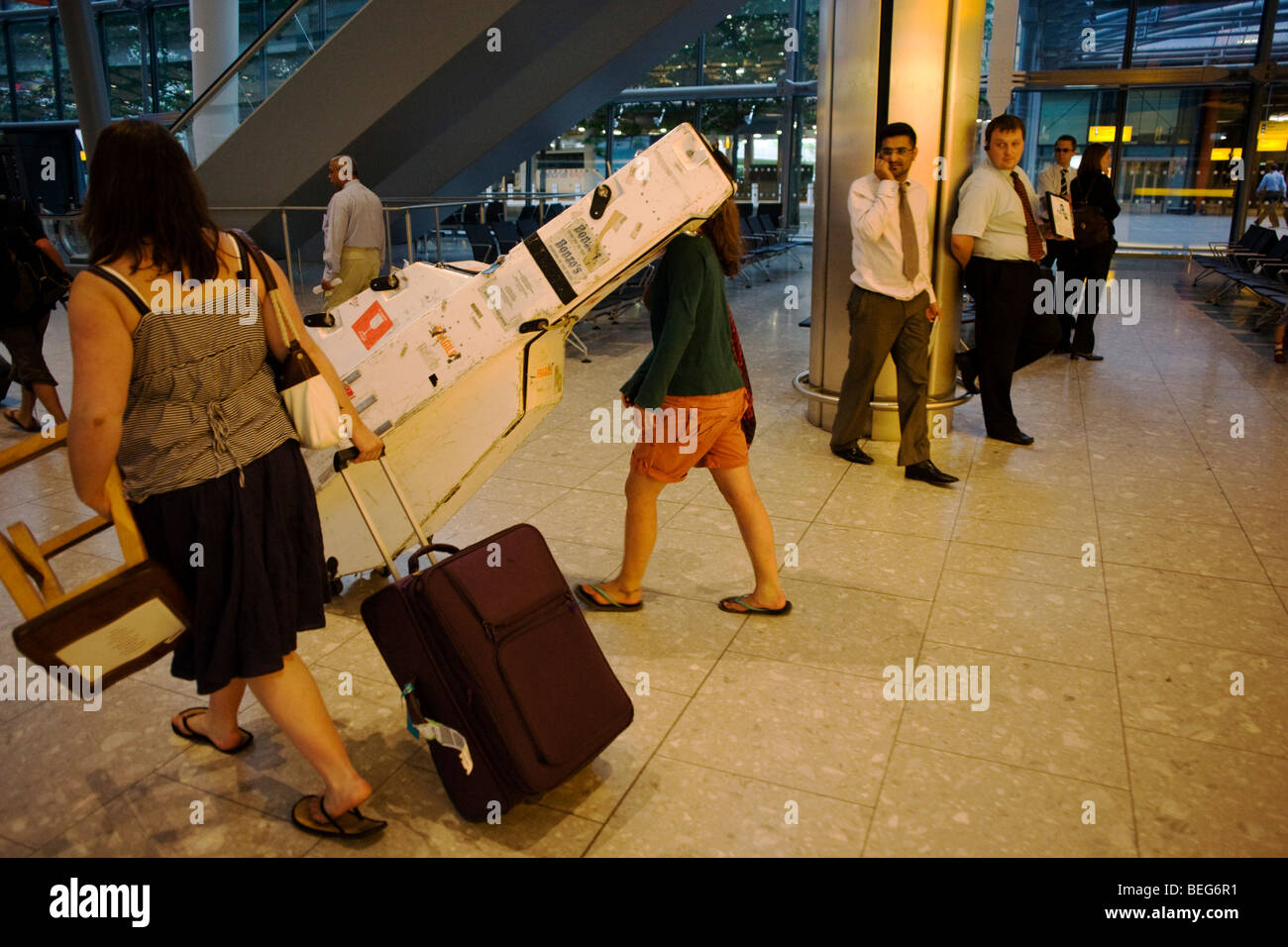 School musicians head for waiting coaches, one with a double-bass in Arrivals at Heathrow's terminal 5. - Stock Image