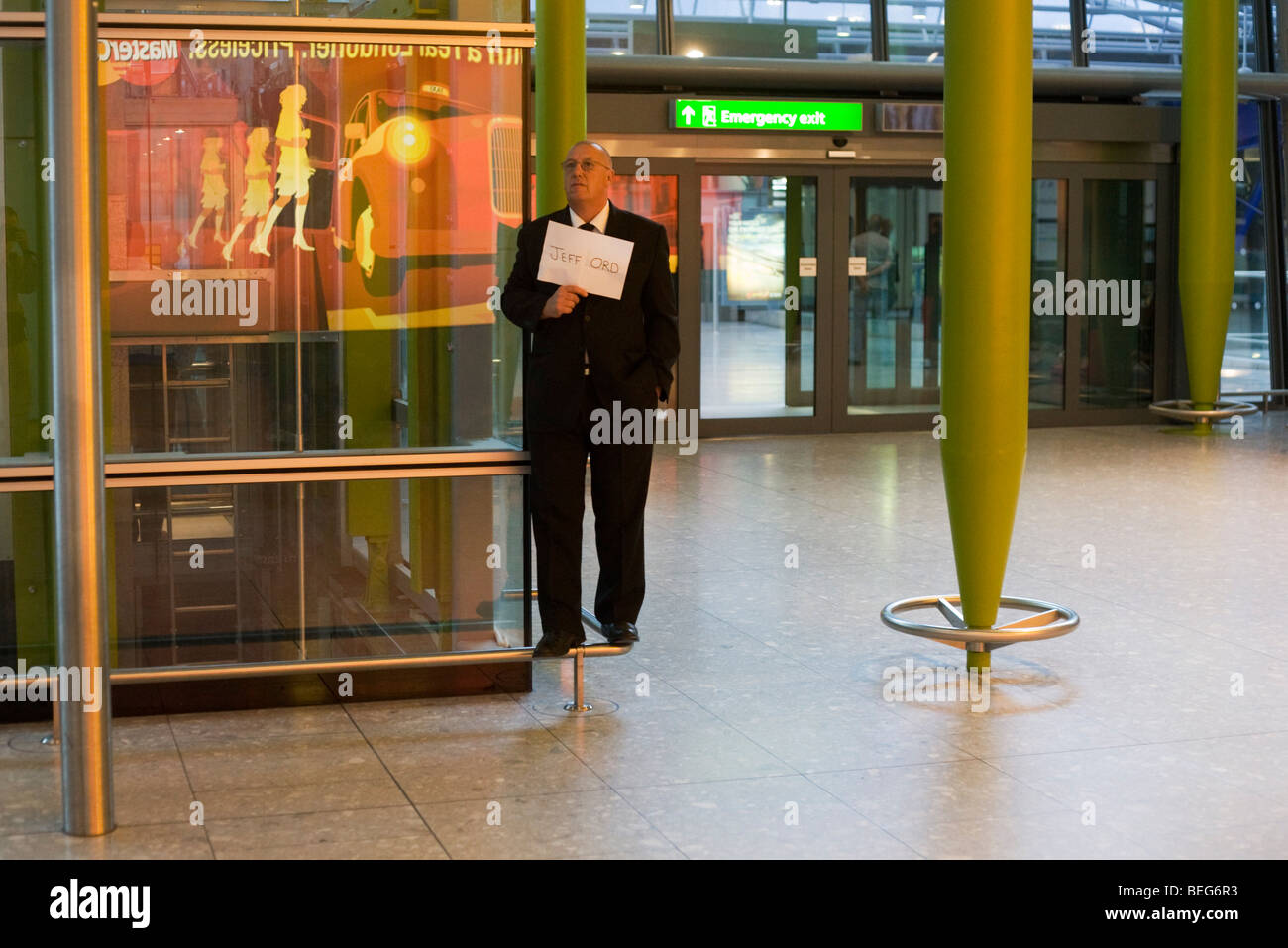 Greeting driver holding passenger name card in Arrivals at Heathrow's Terminal 5. - Stock Image