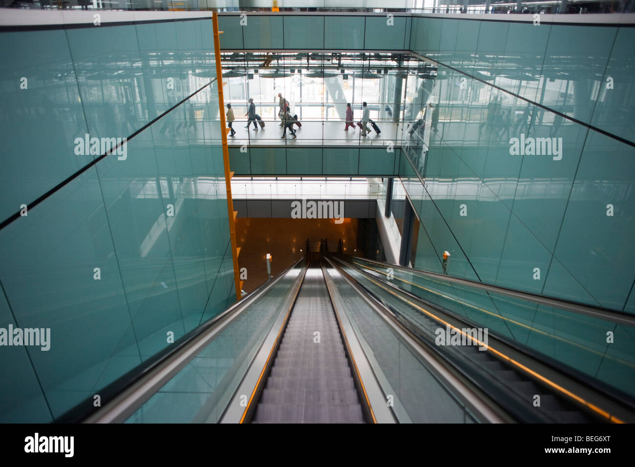 Long escalator and arriving passengers and airport architecture at Heathrow's Terminal 5. - Stock Image