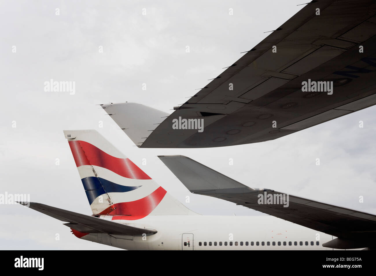 Wing tips and tail from British Airways 747 airliners are almost touching during their turnarounds while on apron - Stock Image