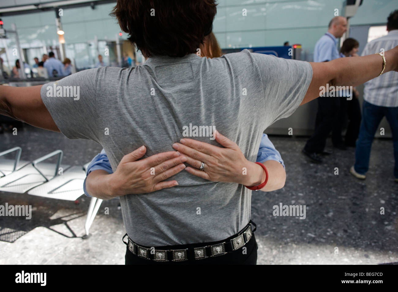 Female security operative feels around a male passenger's back for suspect items during search at Heathrow Airport's - Stock Image