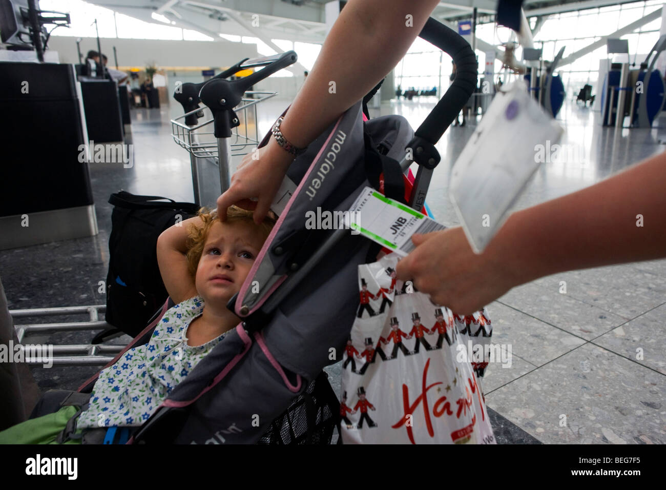 Young girl sits in pushchair as a child-friendly British Airways check-in lady attaches airline tag at Heathrow - Stock Image