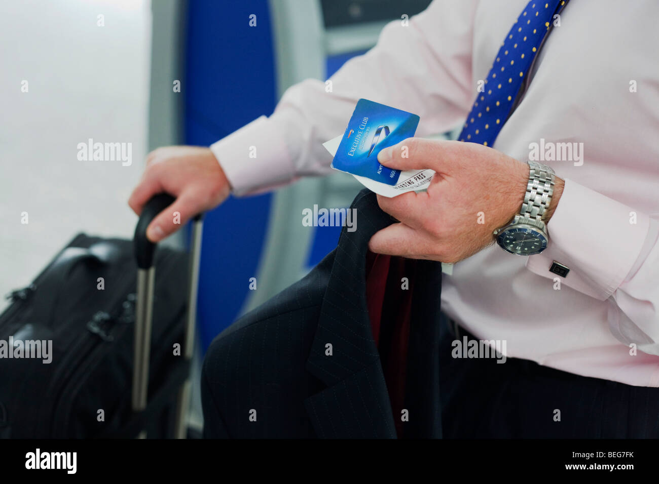 A businessman holds travel documents as he checks-in at the British Airways self-ticketing kiosk at Heathrow's - Stock Image