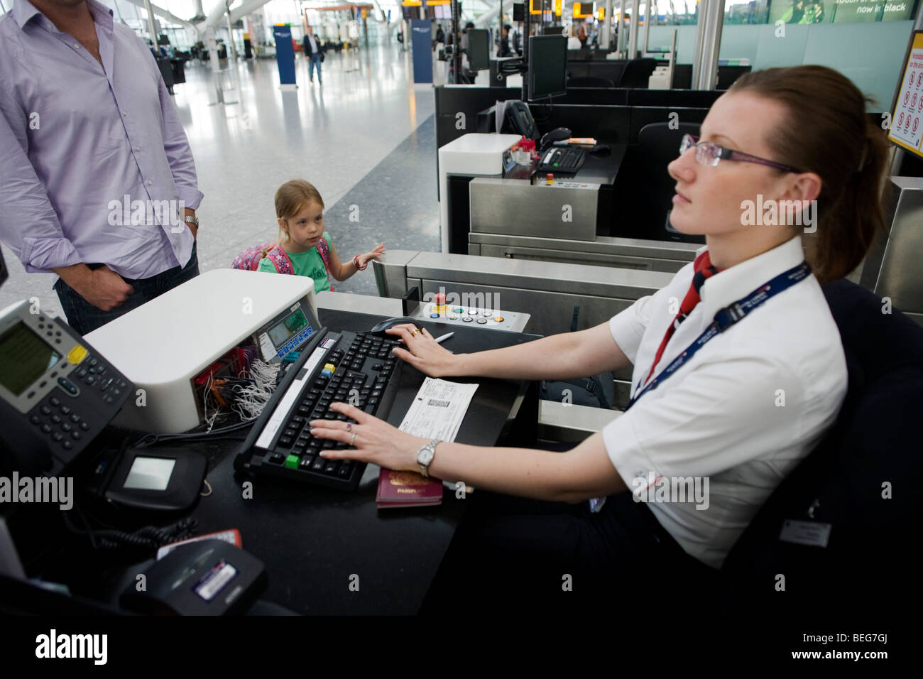Young girl and her father check-in for a British Airways flight at Heathrow Airport's Terminal 5. - Stock Image