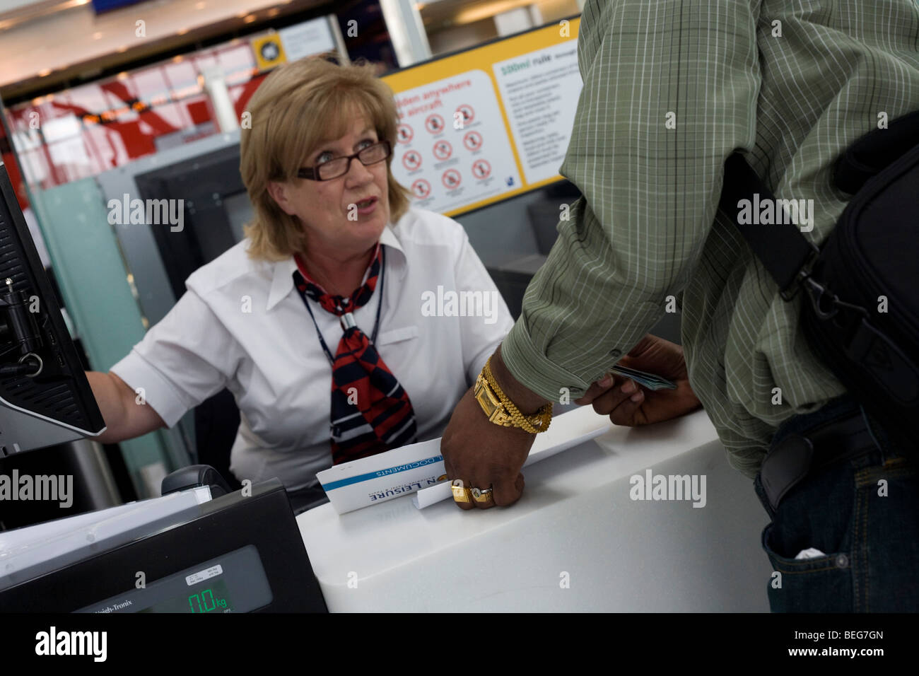 Mature lady employee shows passenger where departures gate is at British Airways check-in at Heathrow Airport's - Stock Image