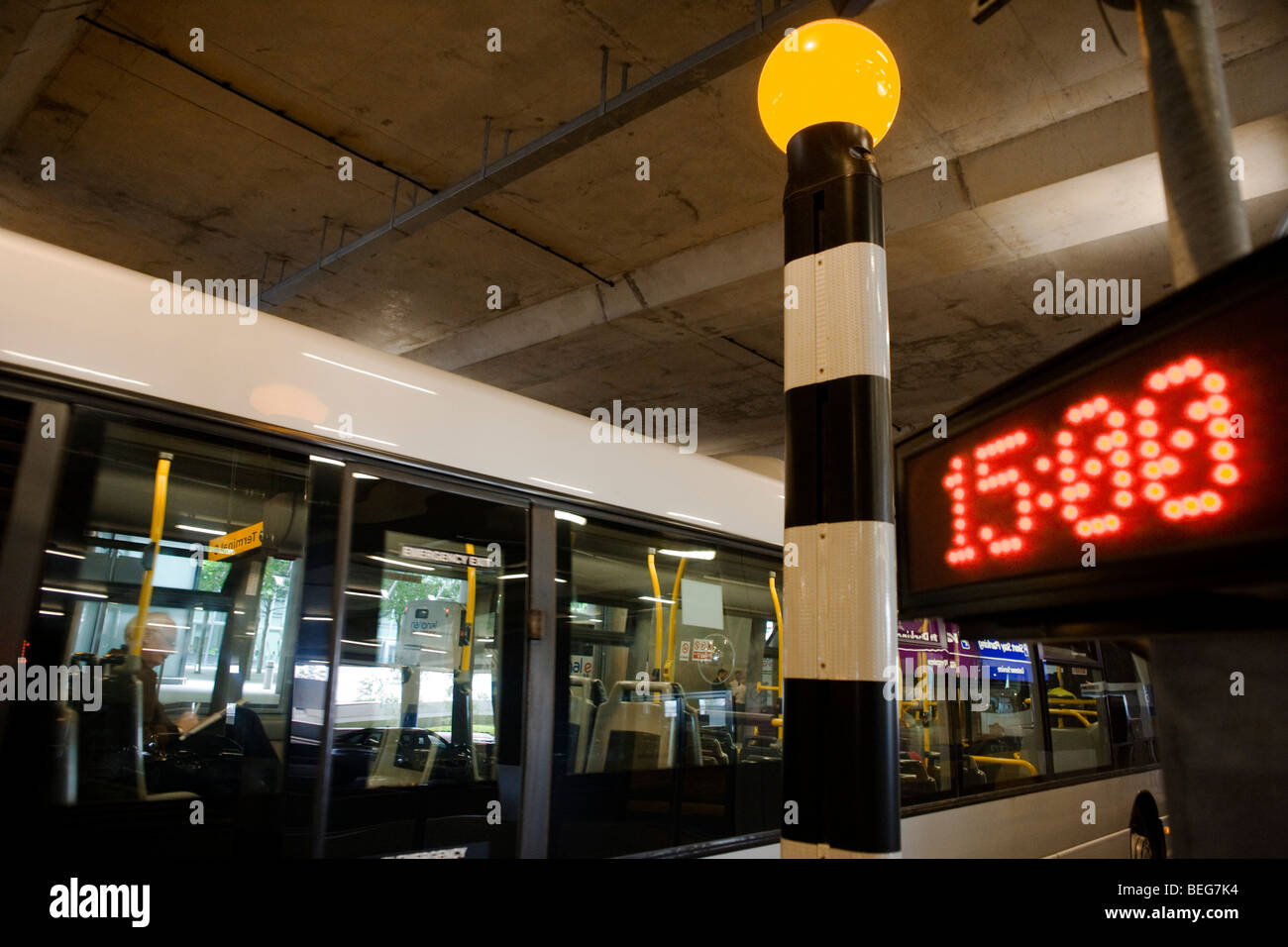 Passing bus and passenger inside with beletia beacon and current time of three o'clock in bus station at Heathrow's - Stock Image