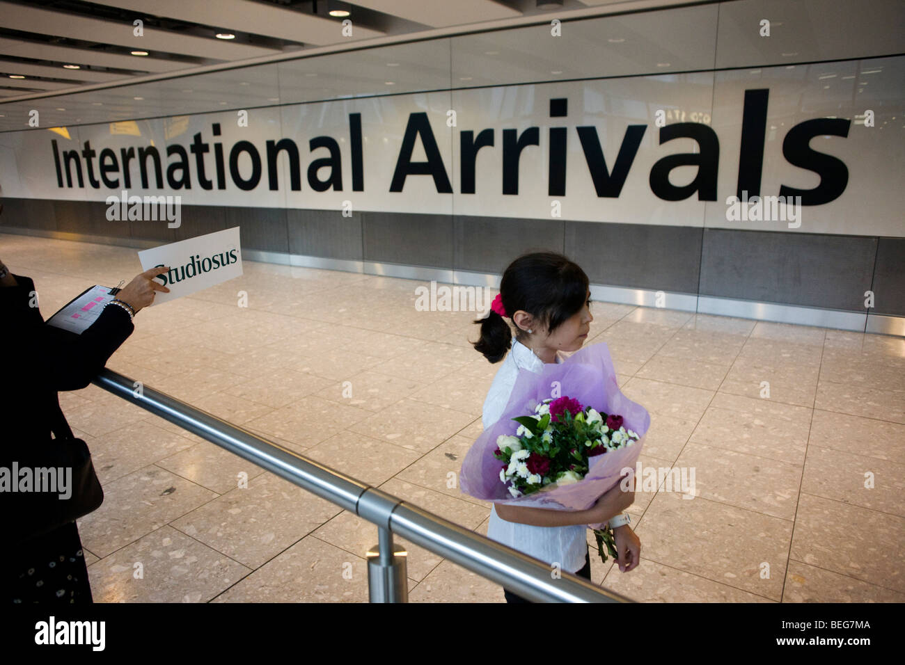Awaiting loved-ones in International Arrivals concourse at Heathrow's terminal 5. - Stock Image