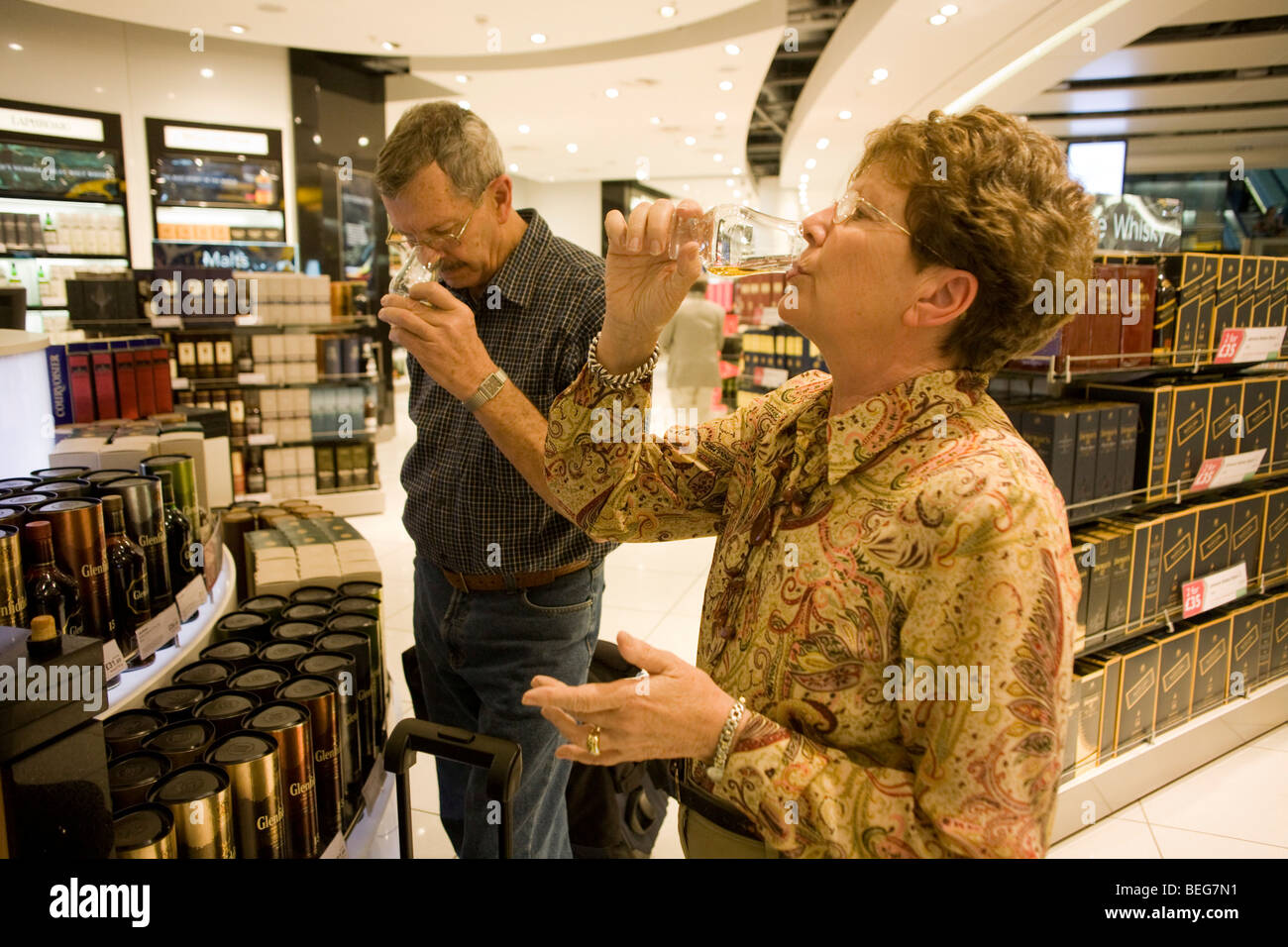Two elderly passengers taste Scottish Malt Whiskey in a retail space called World of Duty Free in Heathrow airport's - Stock Image