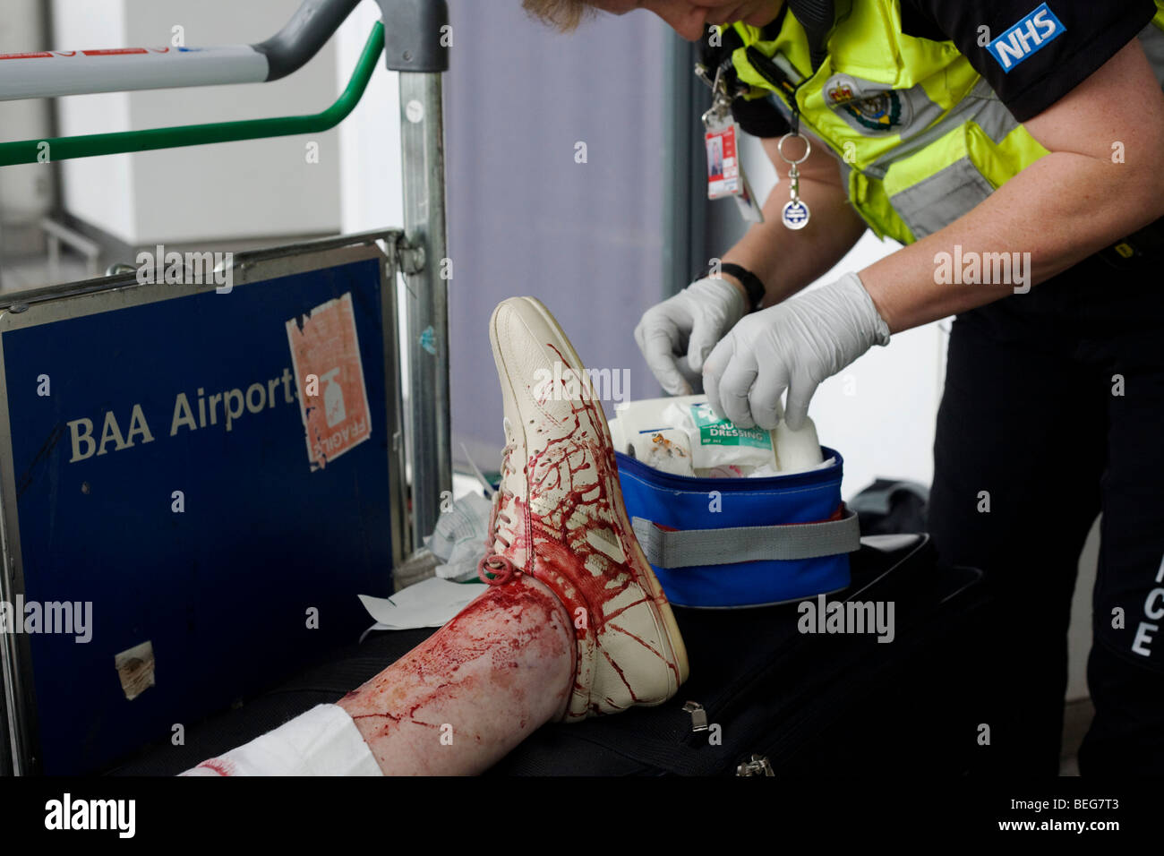 An NHS Paramedic Responder attends a lady passenger in Heathrow's terminal 3 who has tripped and badly gashed - Stock Image
