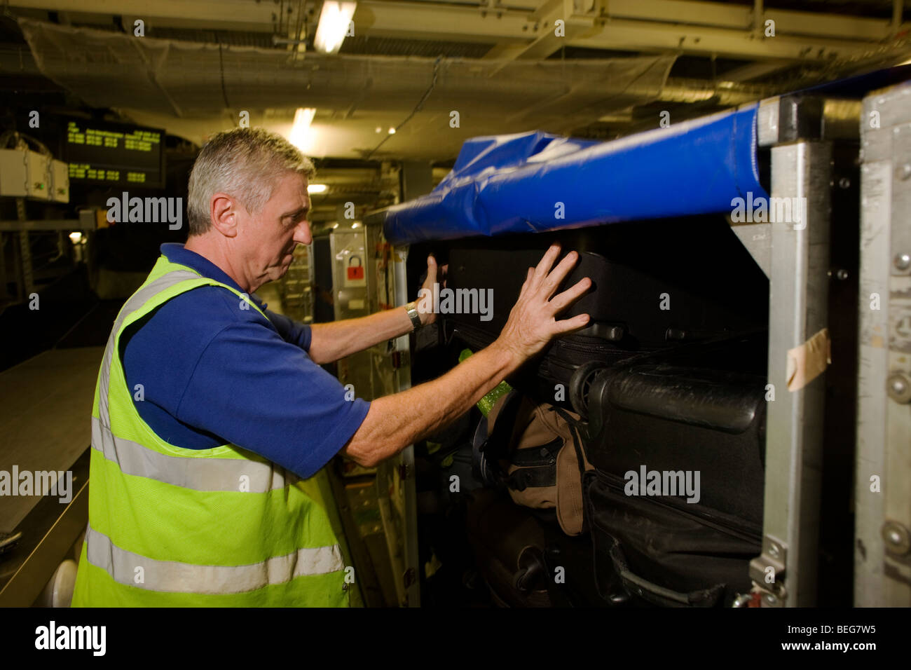 A British Airways baggage loads passengers' possessions into an airline container at Heathrow terminal 5. - Stock Image