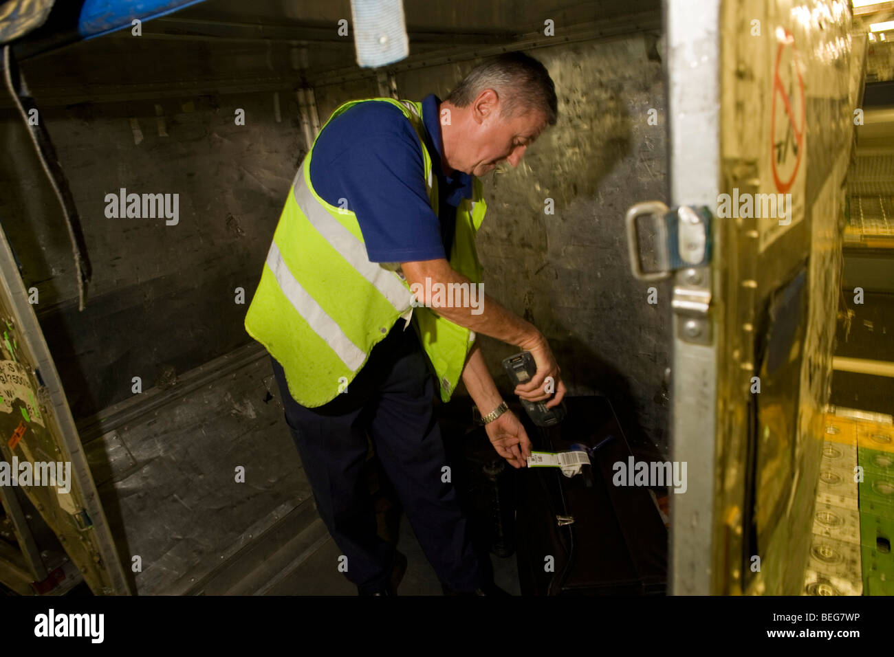 A British Airways baggage handler scans the bar code of his airline passenger's item of luggage before loading - Stock Image