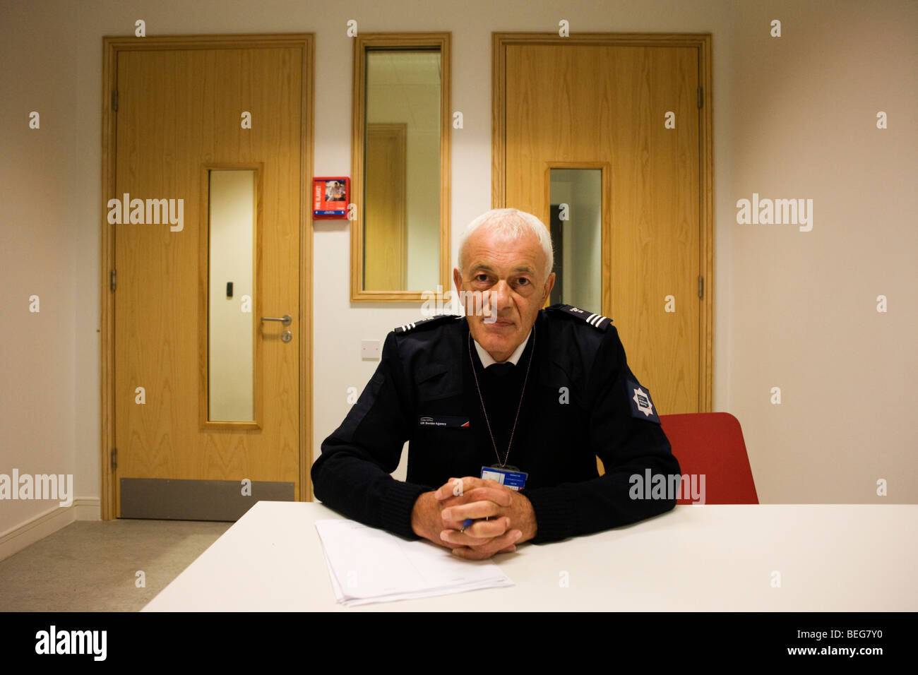 An unnamed Immigration Officer (IMO) with the UK Border Agency sits in a detention interview room Heathrow Airport's - Stock Image