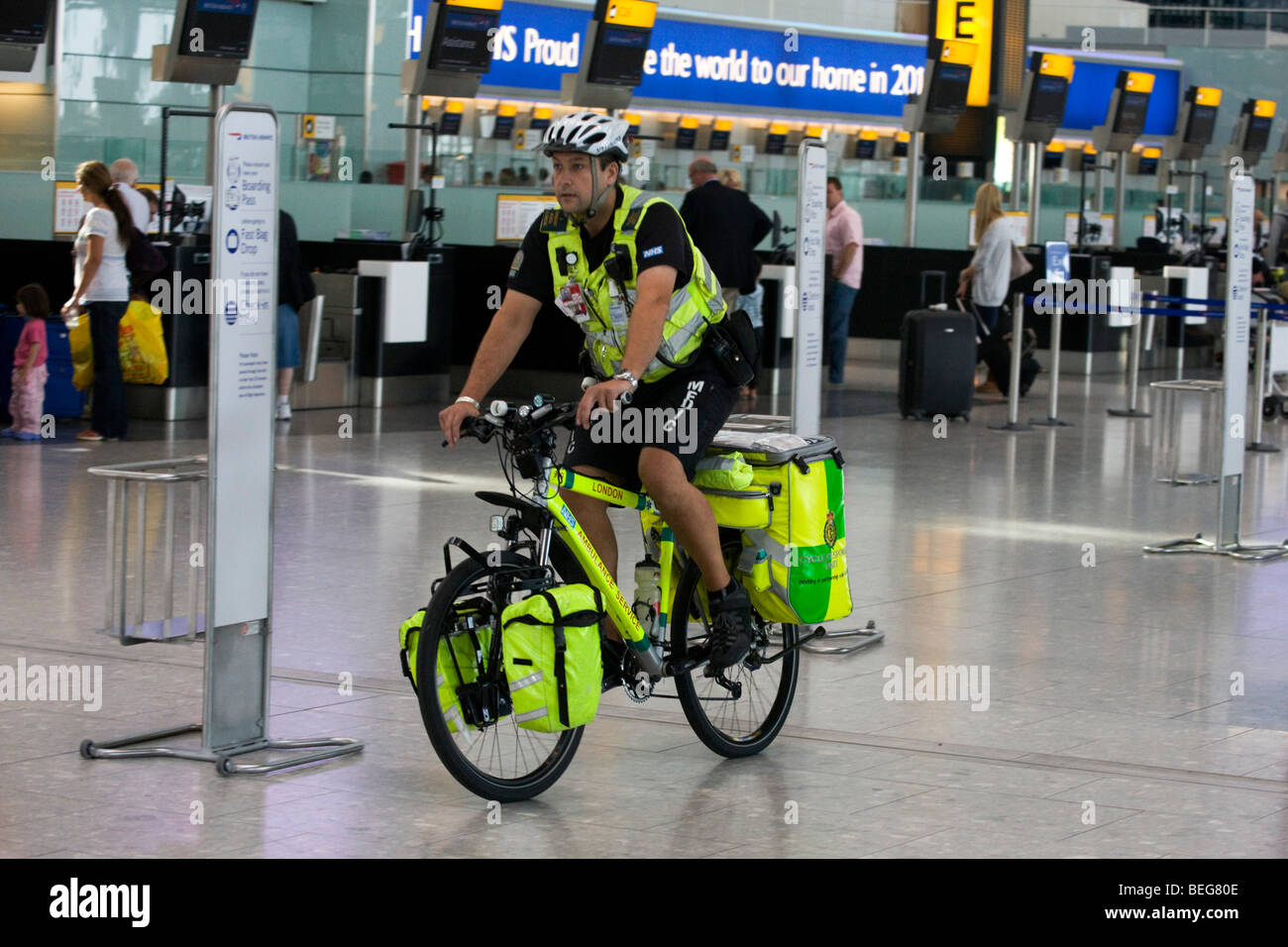 An NHS Paramedic Responder rides his 55kg Specialized Rockhopper mountain bike through in Heathrow's Terminal - Stock Image