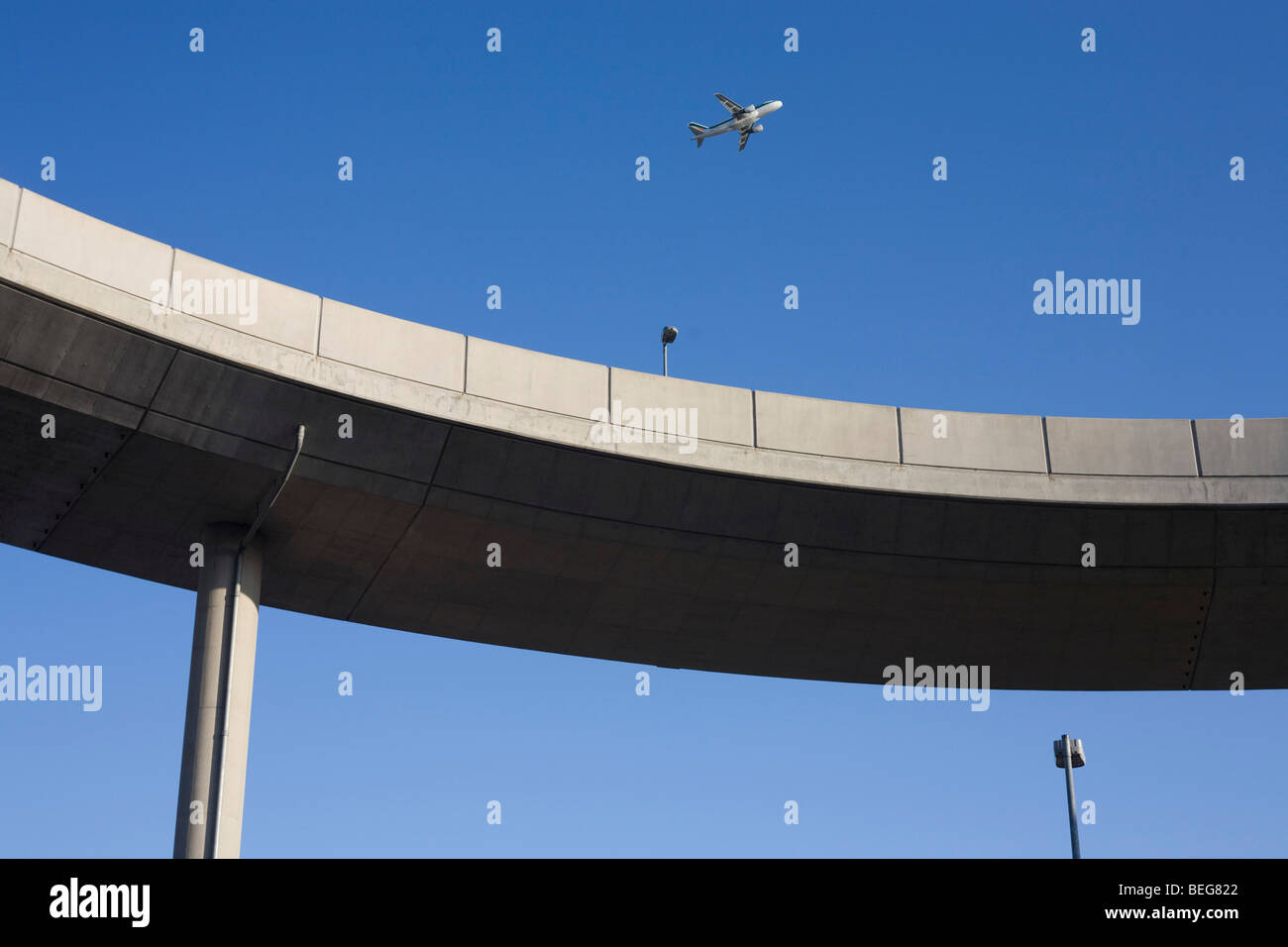 A jet airliner climbs away as it takes-off over a traffic ramp at Heathrow Airport's Terminal 5. - Stock Image