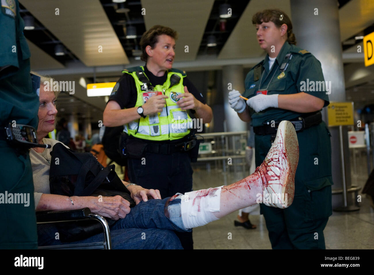 NHS Paramedic Responders attends a lady passenger in Heathrow's terminal 3 who has tripped and badly gashed - Stock Image