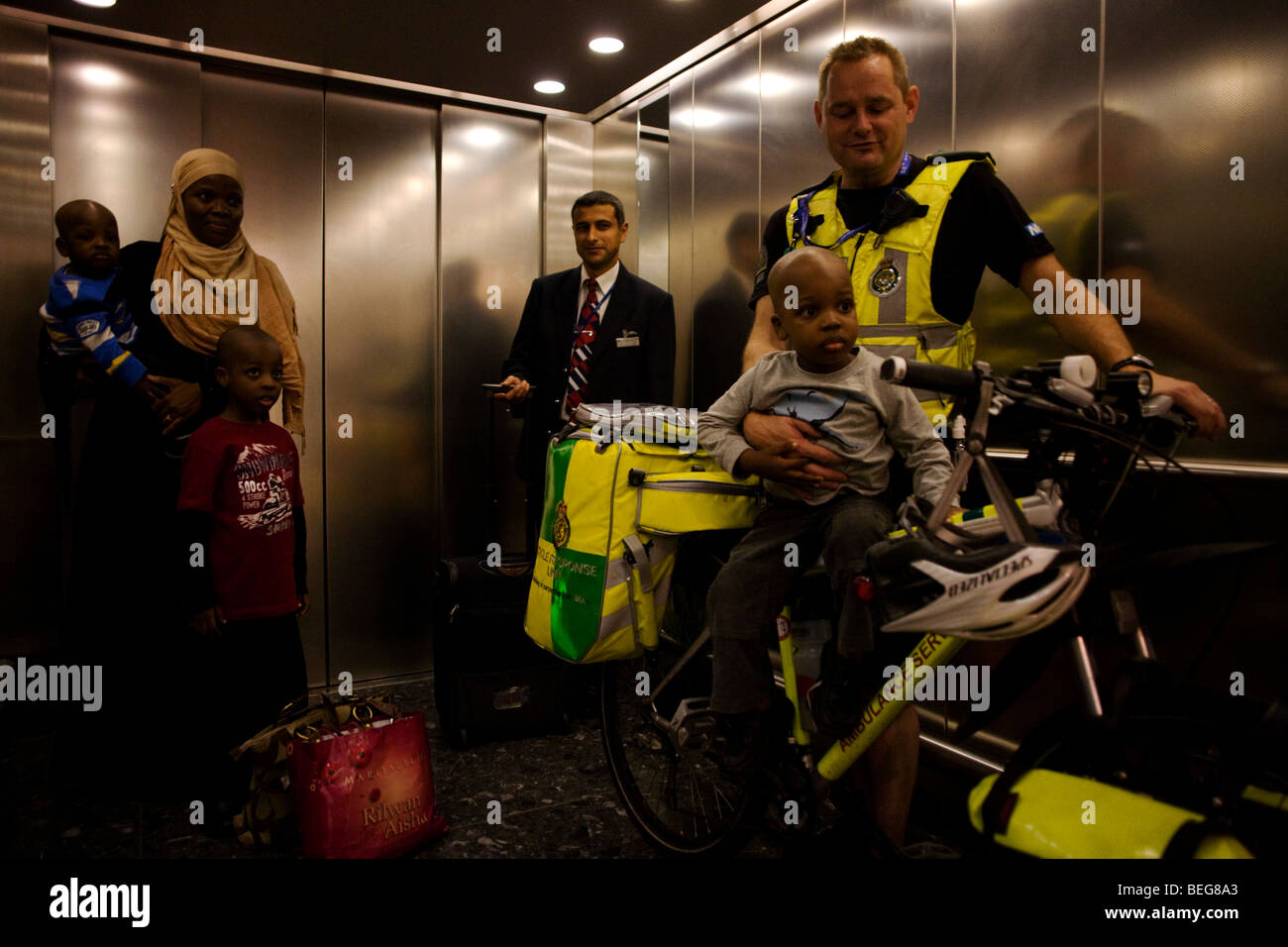 NHS Paramedic cyclist Responders holds a young passenger in a lift (elevator) within Heathrow Airport's terminal - Stock Image