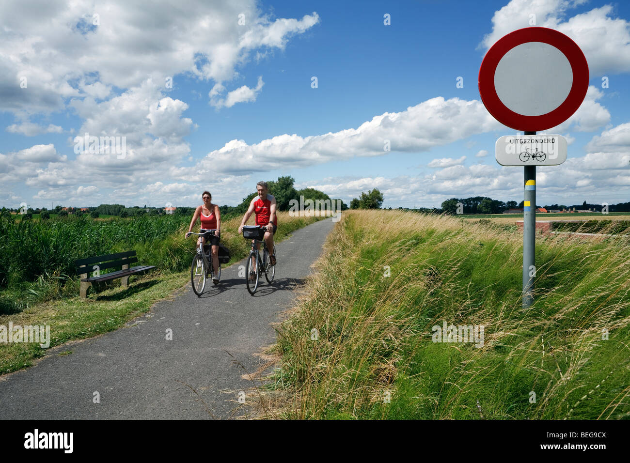 Cyclists on cycle path through North Belgian countryside. - Stock Image