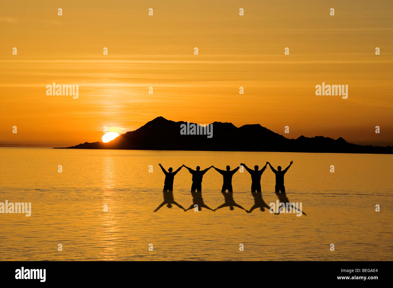 Reflection of friends celebrating in the ocean. - Stock Image