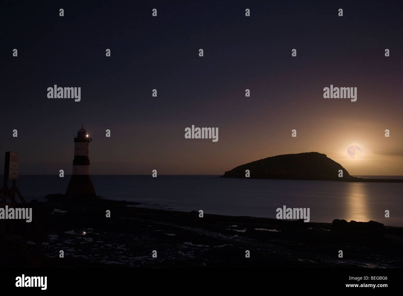 Penmon Lighthouse at dusk with full moon rising by Puffin Island at low tide. Penmon Point Anglesey North Wales - Stock Image