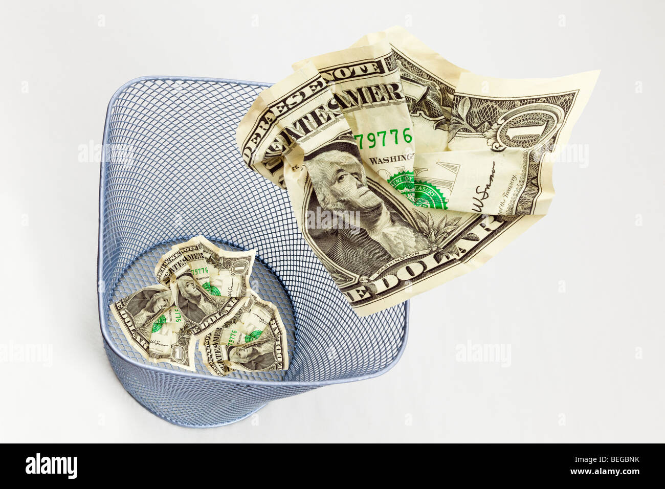 composite image of US dollar bills dollars being thrown into a waste paper bin on plain background from above to - Stock Image